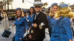 Frank as a pilot hooking arms with several flight attendants.